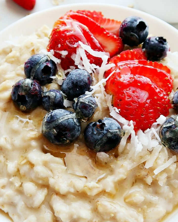 Oatmeal with strawberries and blueberries in a white bowl.