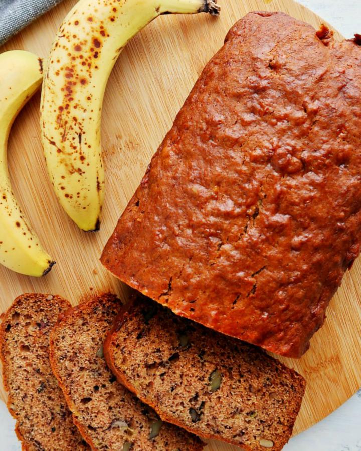 Banana bread and bananas on a cutting board.