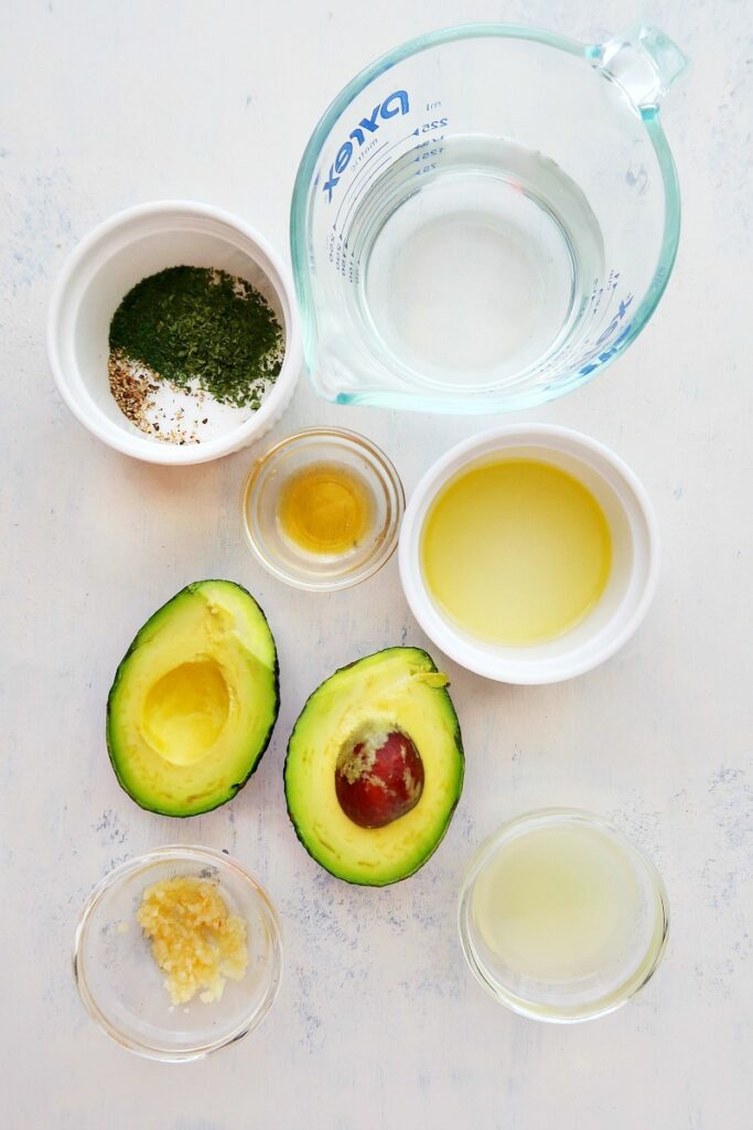 Ingredients for avocado salad dressing on a board.