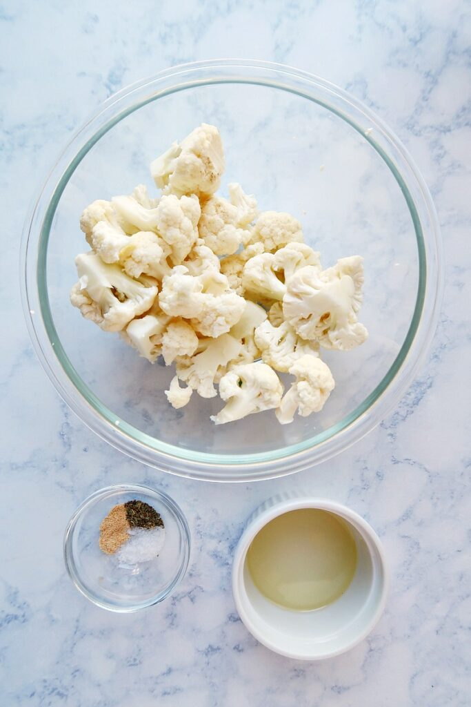 Ingredients for roasted cauliflower on a board.