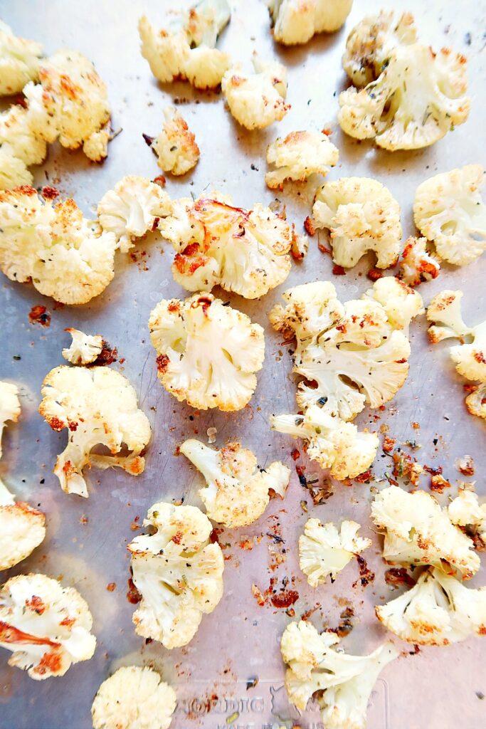 Roasted cauliflower spread on a sheet pan.