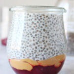 Jam, peanut butter, and chia pudding in a jar on a board.
