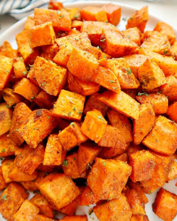 Plate of roasted sweet potatoes on a board.